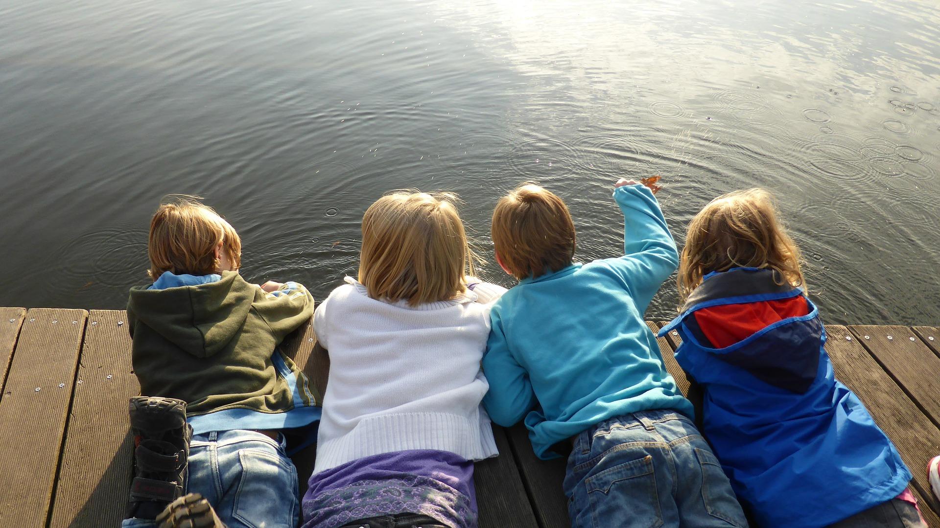 niños y niñas tumbados junto a un lago