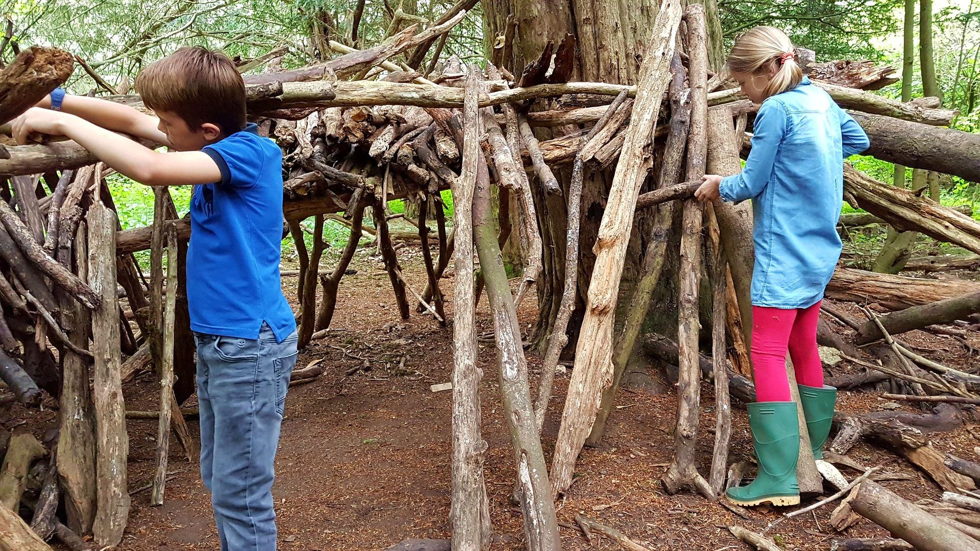 niño y niña haciendo una cabaña con troncos secos