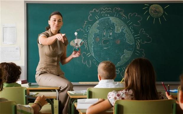 profesora con una pizarra al fondo en la que hay dibujado el planeta tierra