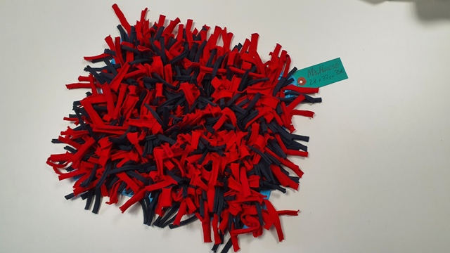 alfombra en colores azul y rojo, de 28 por 32 cm y flexible, etiqueta verde. 35€