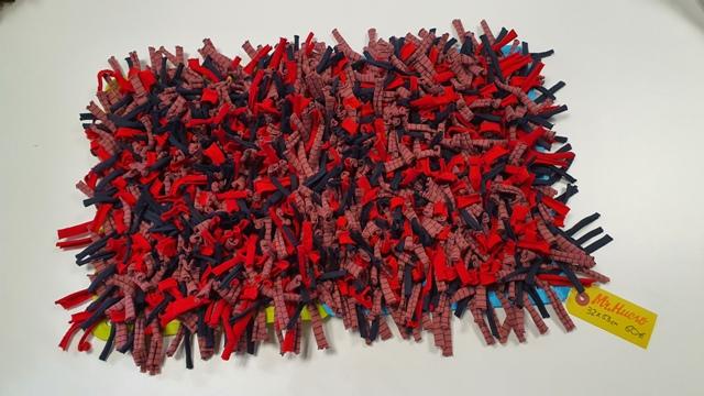 alfombra en tonos rojo, azul y rosa pálido, de 32 por 53 cm y flexible, etiqueta amarilla 60€