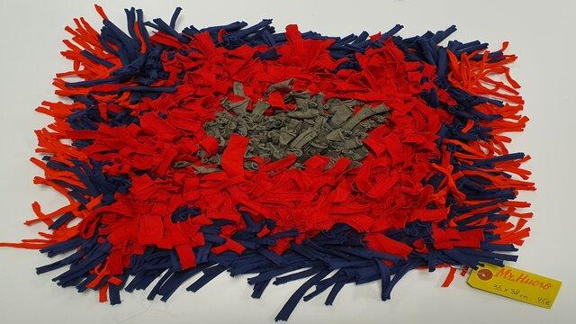alfombra olfativa de colores azul rojo y gris, mide 33 por 38cm y cuesta 45€, etiqueta amarilla