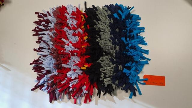 alfombra de muchos colores, azul, negro, gris, rojo, blanco y violeta, a franjas. mide 33 por 38 cm y cuesta 45€, tiene etiqueta naranja