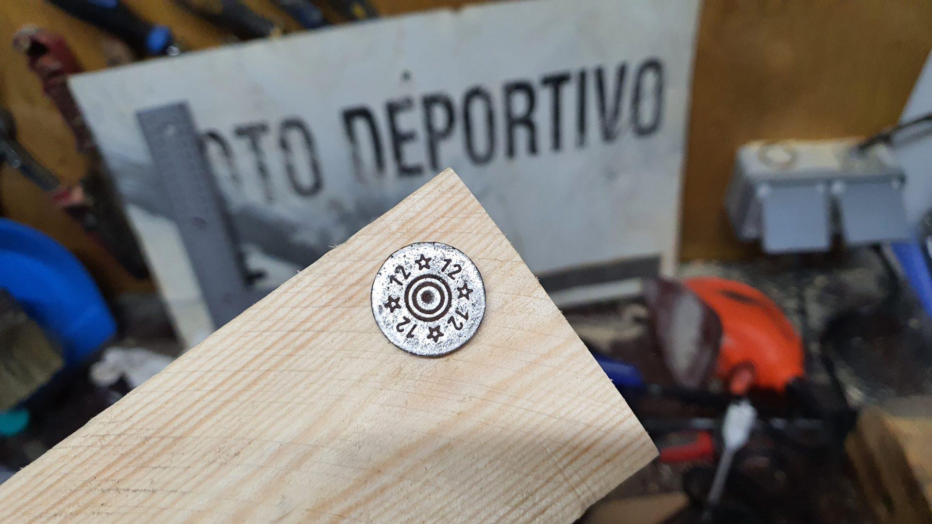 Detalle de un cartucho encastrado en la madera, se ve que son de calibre 12